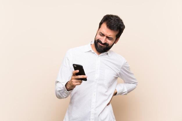 Młody człowiek trzyma brodę cierpiącą na ból pleców z powodu wysiłku