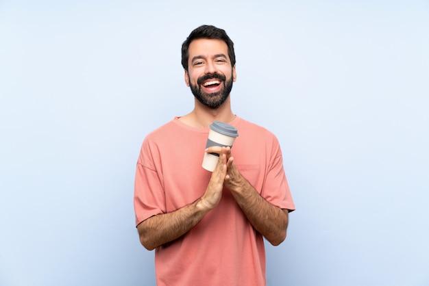 Młody człowiek trzyma brodę kawę nad odosobnioną błękit ścianą oklaskuje po prezentaci w konferenci z brodą