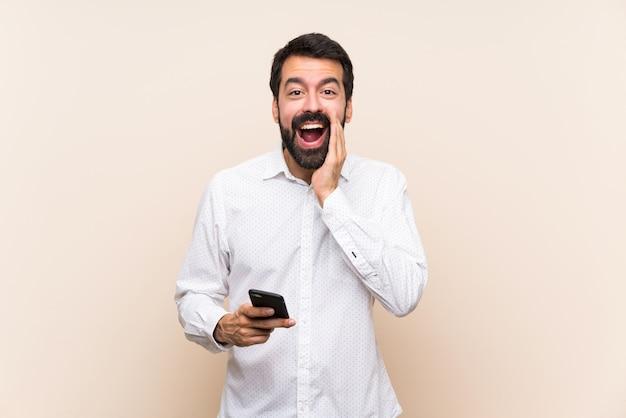 Młody człowiek trzyma brodę krzyczy coś i ogłasza coś