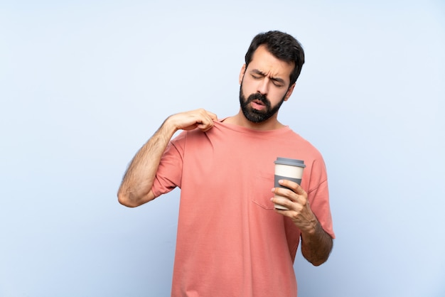 Młody człowiek trzyma brodę zabiera kawę na błękicie z zmęczonym i chorym wyrażeniem z brodą