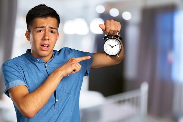 Młody człowiek trzyma budzika
