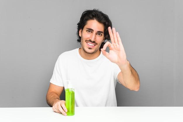 Młody człowiek trzyma butelkę aloesu wesoły i pewny siebie pokazując gest ok.