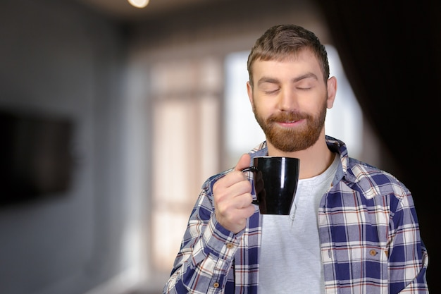 Młody człowiek trzyma ciepłą filiżankę herbata / kawa