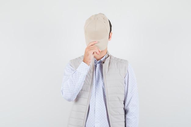 Młody człowiek trzyma czapkę na twarzy w koszuli, kurtce bez rękawów i szuka sekretu. przedni widok.
