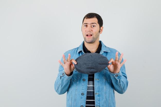 Młody człowiek trzyma czapkę w kurtce, t-shirt i niepewny patrząc.
