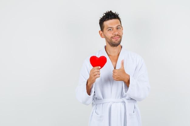 Młody człowiek trzyma czerwone serce z kciukiem w biały szlafrok i wygląda radośnie. przedni widok.