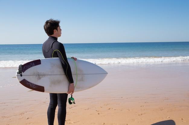 Młody człowiek trzyma deskę surfingową i patrzeje morze