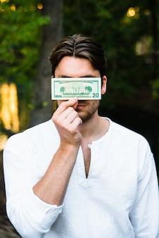 Młody człowiek trzyma dolarowego rachunek przed jego twarzą, korupci pojęcie.