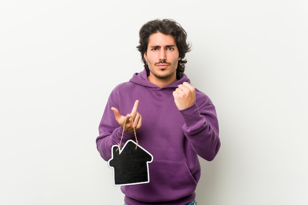 Młody człowiek trzyma domowego ikona kształt pokazuje pięść kamera, agresywny wyraz twarzy.