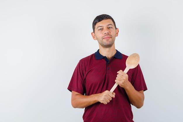 Młody człowiek trzyma drewnianą łyżkę w t-shirt i wygląda wesoło. przedni widok.