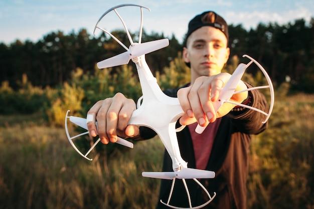 Młody człowiek trzyma drona obiema rękami