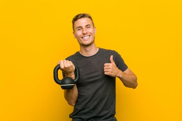Młody człowiek trzyma dumbbell uśmiecha się kciuk up i podnosi