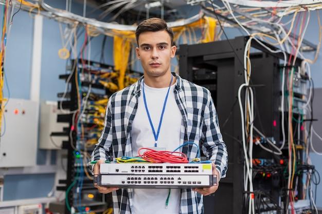Młody człowiek trzyma ethernetowe przełączniki