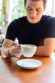 Młody człowiek trzyma filiżankę gorąca kawa