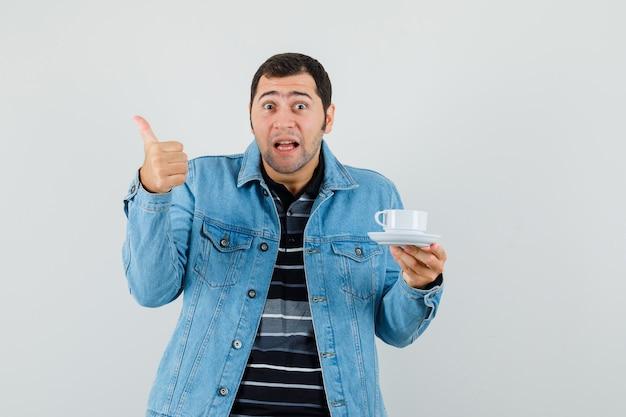 Młody człowiek trzyma filiżankę herbaty, pokazując kciuk w t-shirt, kurtkę i patrząc pozytywnie.
