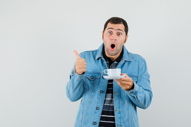 Młody człowiek trzyma filiżankę herbaty, pokazując kciuk w t-shirt, kurtkę i patrząc zdziwiony