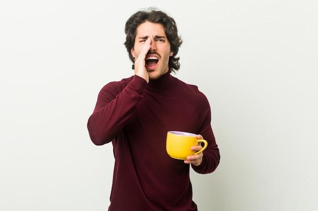Młody człowiek trzyma filiżankę kawy krzyczy podekscytowany do przodu