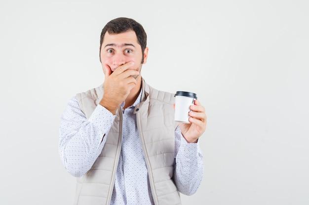 Młody człowiek trzyma filiżankę kawy na wynos i zakrywa usta ręką w beżowej kurtce i wygląda zaskoczony, widok z przodu.