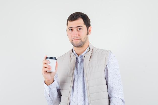 Młody człowiek trzyma filiżankę kawy w beżowej kurtce i czapce i wygląda poważnie. przedni widok.