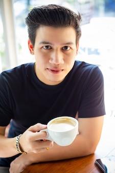 Młody człowiek trzyma filiżankę kawy