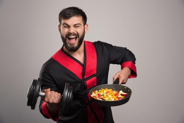 Młody człowiek trzyma hantle i patelnię z warzywami.
