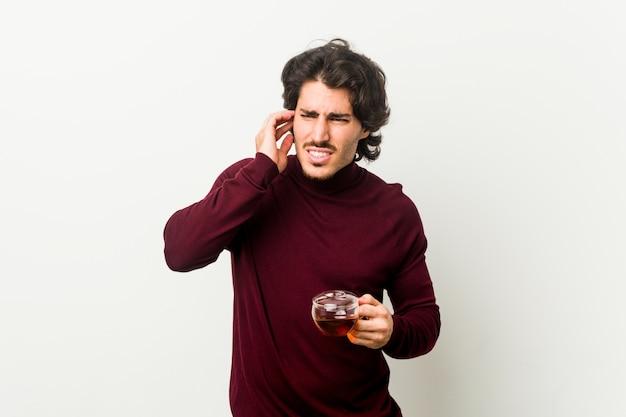 Młody człowiek trzyma herbacianą filiżankę zakrywa ucho z rękami.