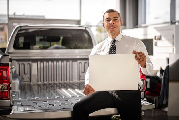 Młody człowiek trzyma kartkę papieru i siedzi z tyłu ciężarówki