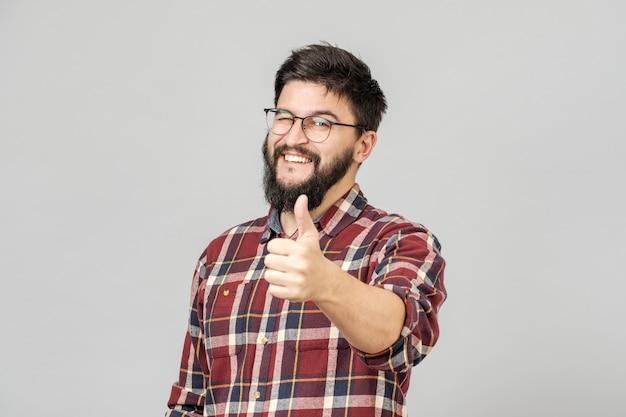 Młody człowiek trzyma kciuk do góry. na szarym tle