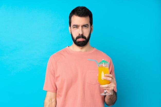 Młody człowiek trzyma koktajl nad odosobnioną błękit ścianą z smutnym i przygnębionym wyrażeniem
