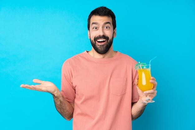 Młody człowiek trzyma koktajl nad odosobnioną błękit ścianą z szokującym wyrazem twarzy