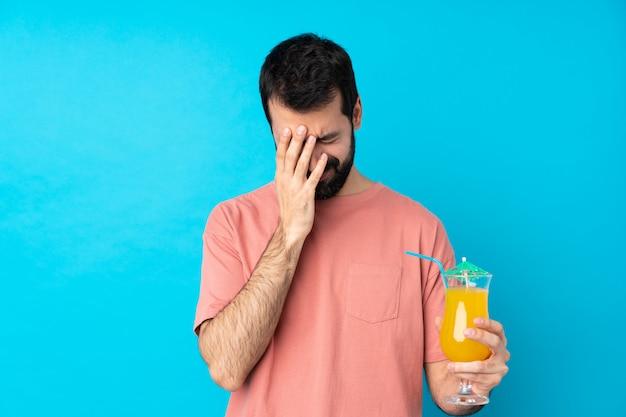 Młody człowiek trzyma koktajl nad odosobnioną błękit ścianą z zmęczonym i chorym wyrażeniem