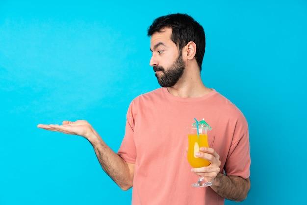 Młody człowiek trzyma koktajl nad odosobnionym błękit ściany mienia copyspace z wątpliwościami