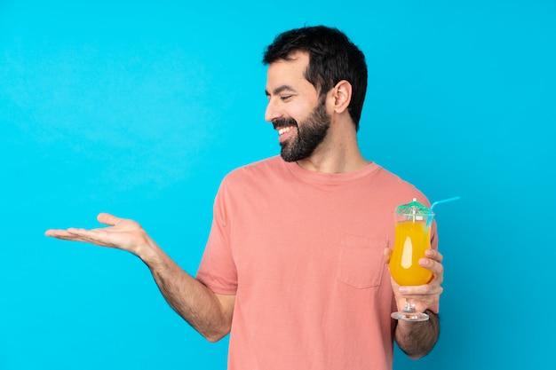 Młody człowiek trzyma koktajlu mienia copyspace z dwa rękami