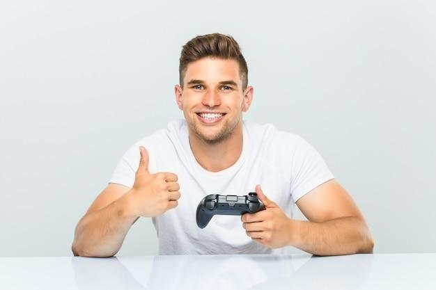 Młody człowiek trzyma kontrolera gier uśmiecha się kciuk up i podnosi