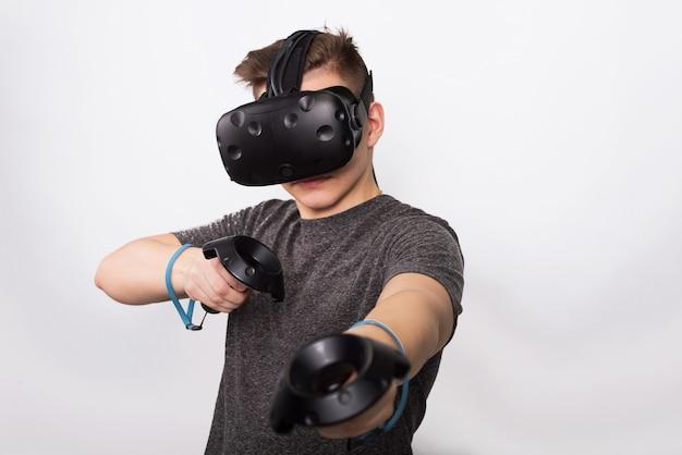 Młody człowiek trzyma kontrolerów dla różnych gier. nastolatek bawi się okularami wirtualnej rzeczywistości i rozważa joysticki i gamepady