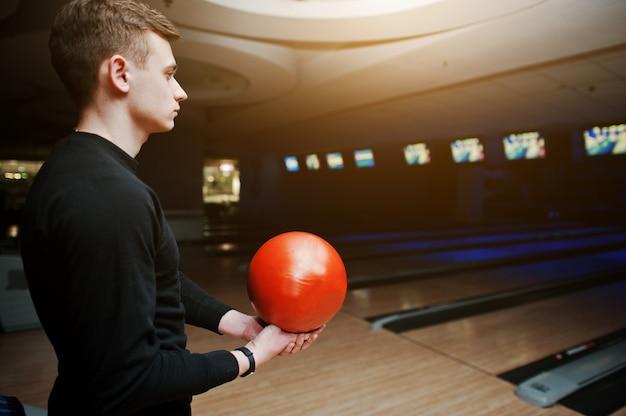 Młody człowiek trzyma kręgle piłkę stojącą przed kręgielnie światłem ultrafioletowym.