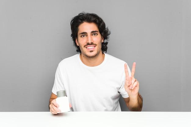 Młody człowiek trzyma krem po goleniu pokazuje zwycięstwo znak i uśmiecha się szeroko.
