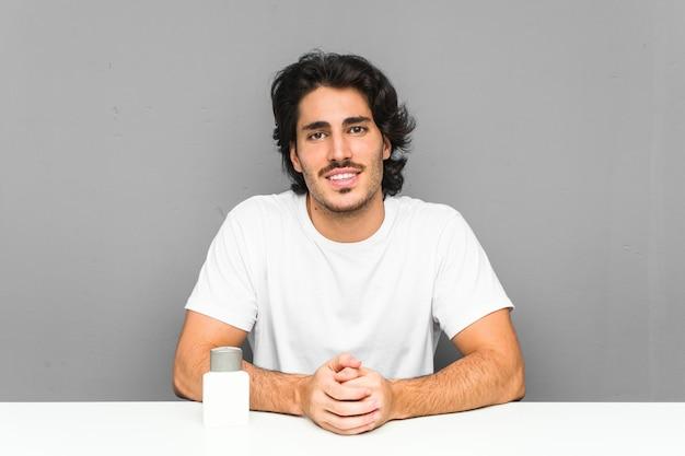 Młody człowiek trzyma krem po goleniu szczęśliwy, uśmiechnięty i wesoły.