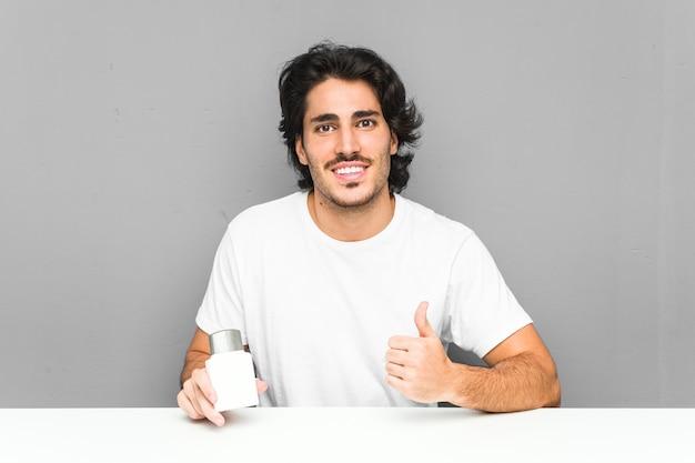 Młody człowiek trzyma krem po goleniu, uśmiechając się i podnosząc kciuk do góry