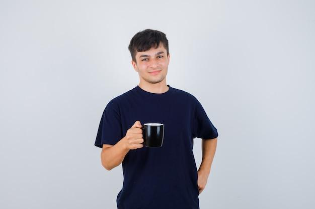 Młody człowiek trzyma kubek napoju w czarnej koszulce i patrząc dumny, przedni widok.