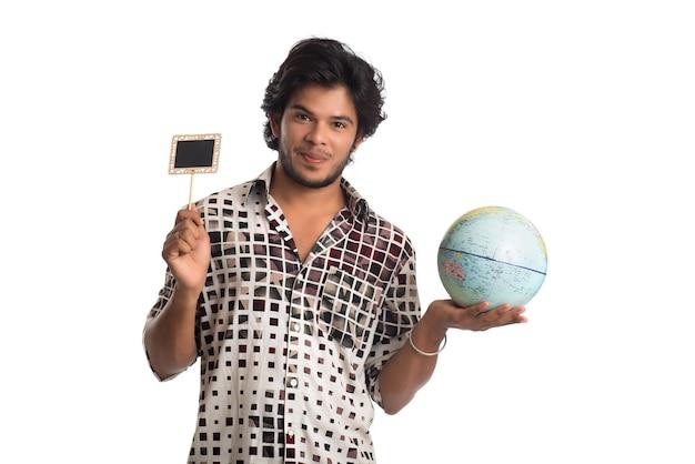 Młody człowiek trzyma kulę ziemską świata i małą deskę na białym.