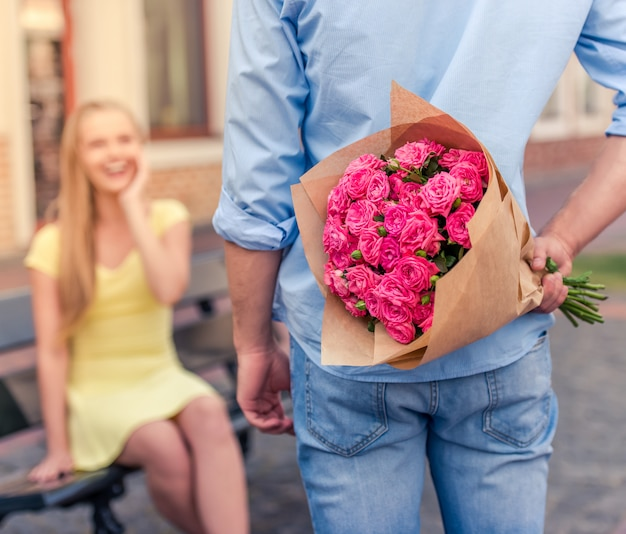 Młody człowiek trzyma kwiaty za jego plecami