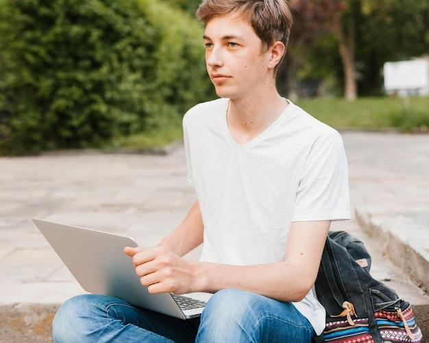 Młody człowiek trzyma laptop w parku