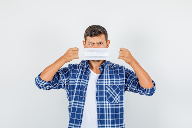 Młody człowiek trzyma maskę medyczną na ustach w koszuli i wygląda ponuro. przedni widok.