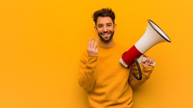 Młody człowiek trzyma megafon pokazuje liczbę trzy