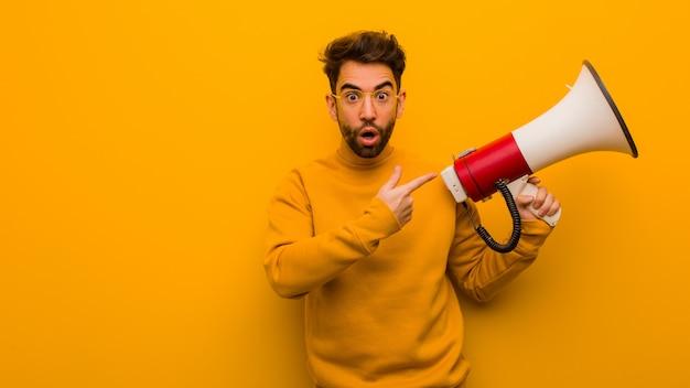 Młody człowiek trzyma megafon trzyma coś z ręką