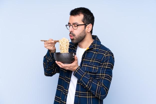 Młody człowiek trzyma miskę makaronu z piasku chopstick dmuchanie go, ponieważ są gorące