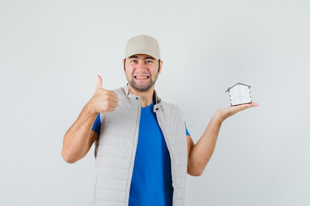Młody Człowiek Trzyma Model Domu, Pokazując Kciuk W T-shirt, Kurtkę, Czapkę I Patrząc Radośnie. Przedni Widok. Darmowe Zdjęcia