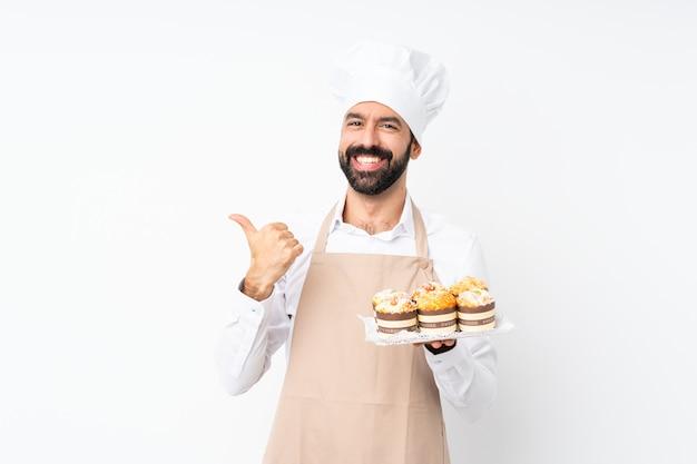 Młody człowiek trzyma muffin tort nad odosobnioną biel ścianą z aprobata gestem i ono uśmiecha się