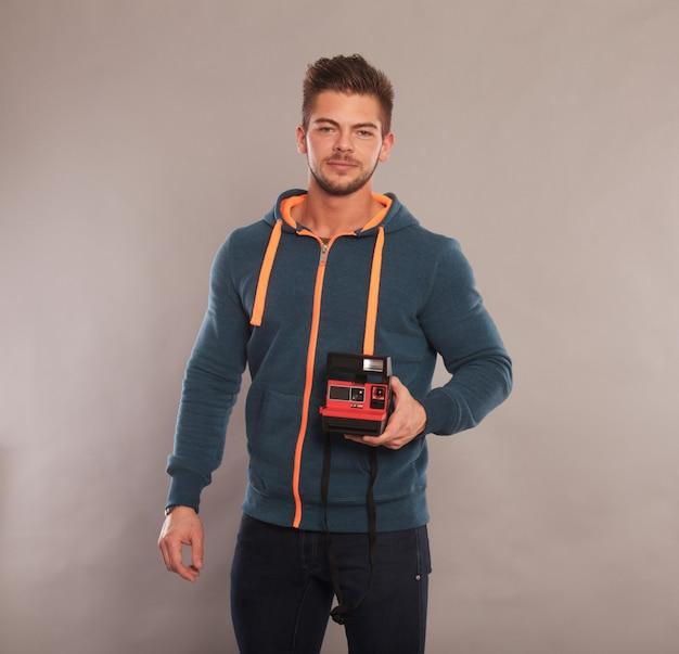 Młody człowiek trzyma natychmiastową kamerę